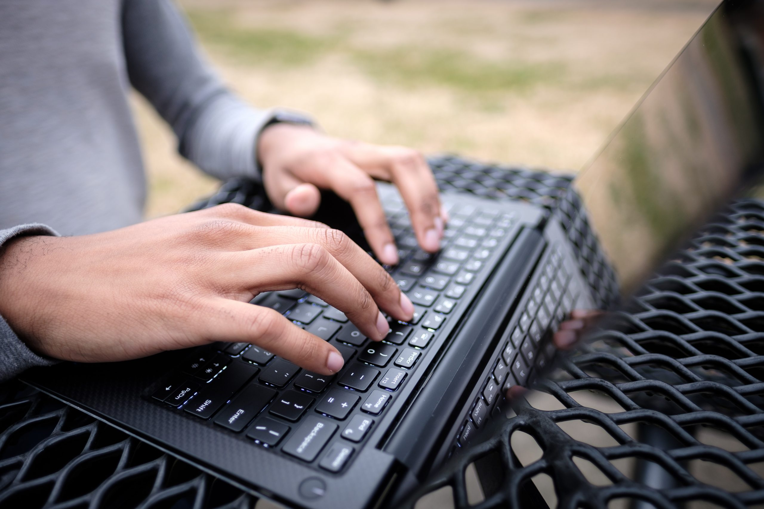 Person typing on laptop on outside table