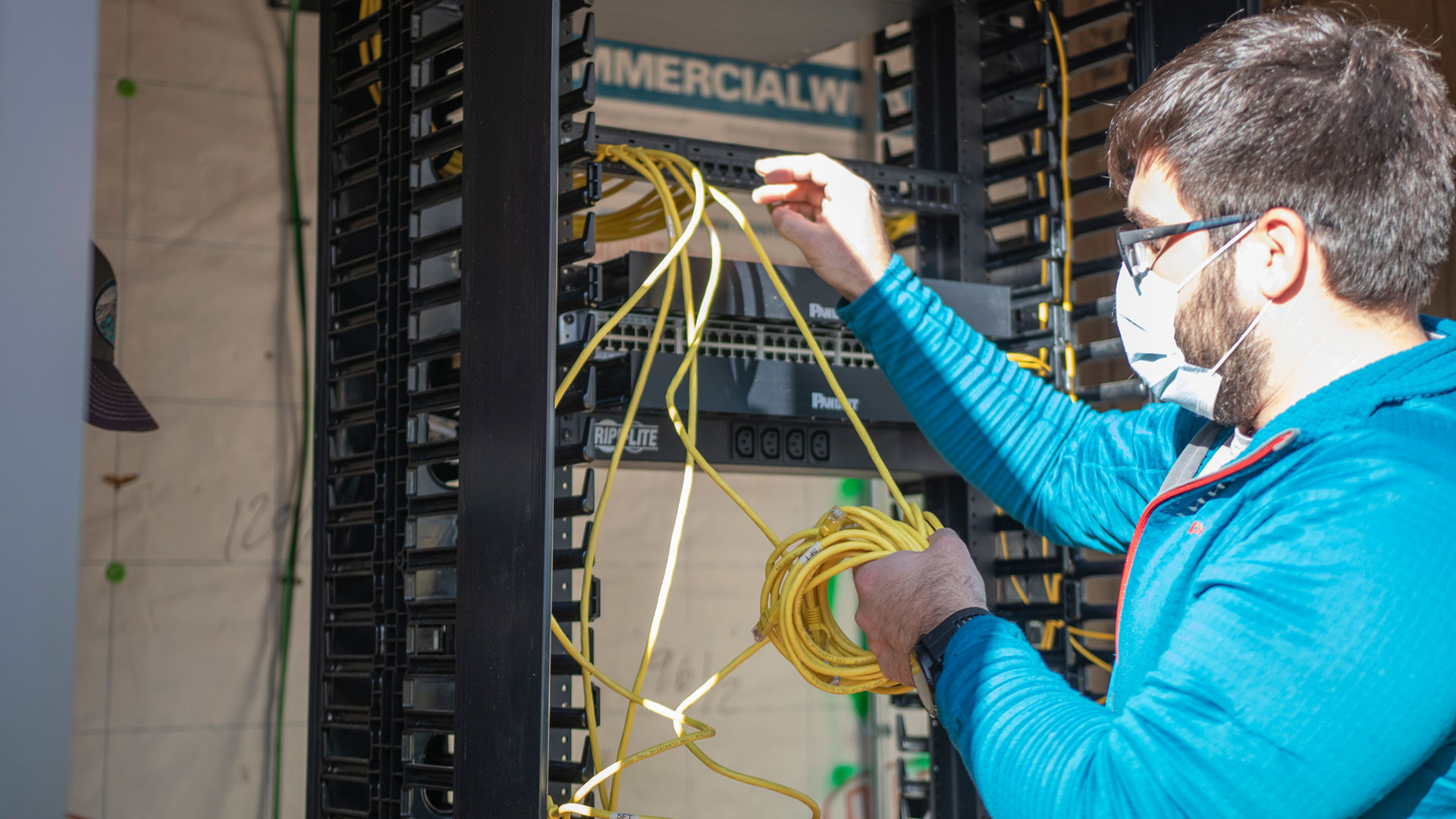Network engineer Jeff Courtney working to install cable in a network closet