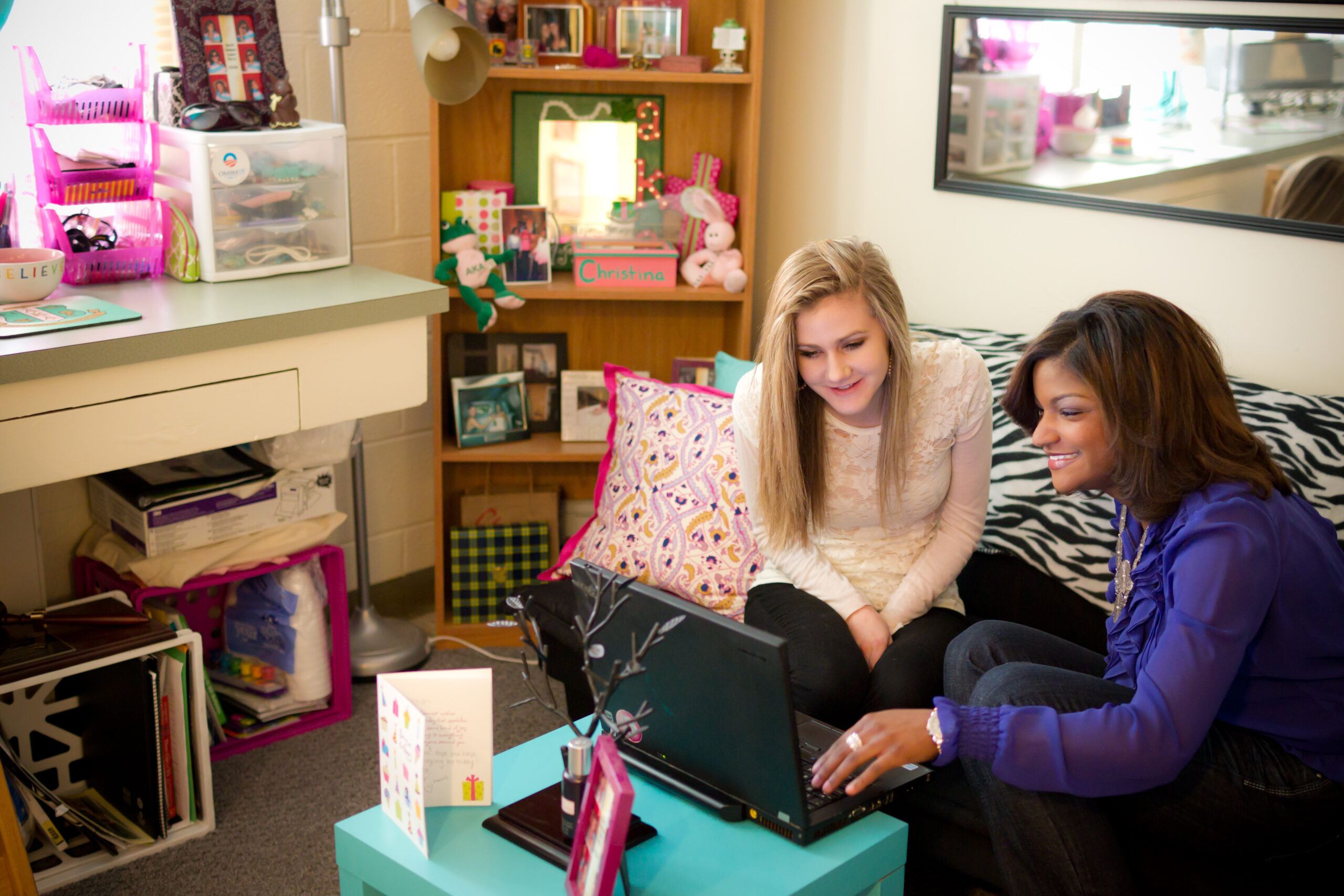 Students share a laptop on a couch inside a residence hall room.