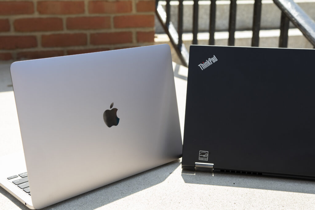 A MacBook Pro and Lenovo ThinkPad side by side